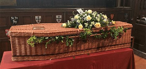 wicker coffin with flowers